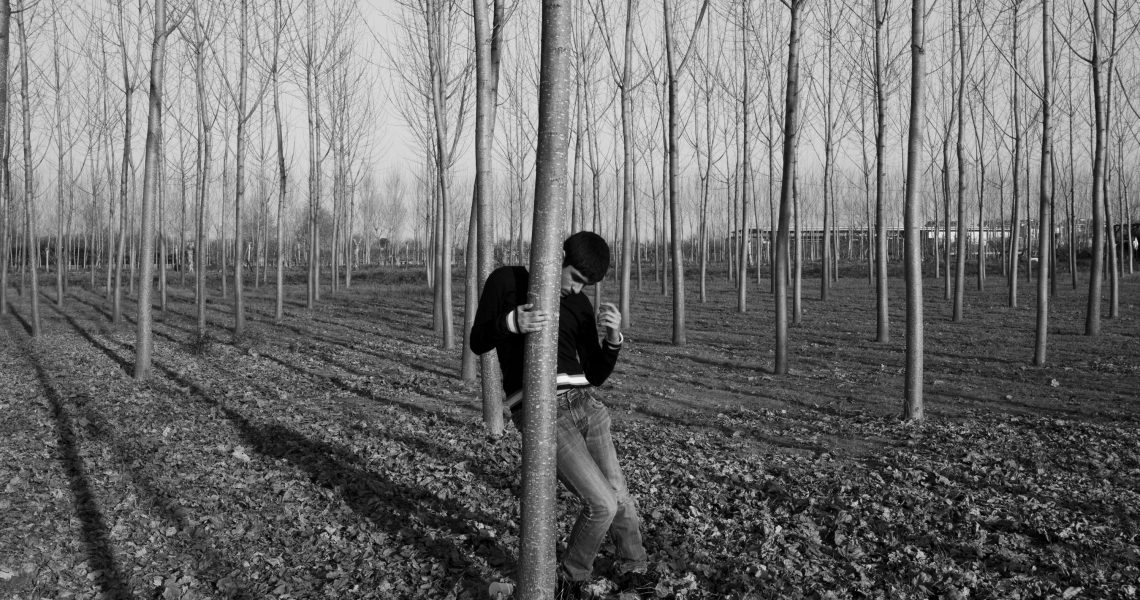 Italy, Casal di Principe (CE), 12/03/2014. Gennaro, one of the two autistic twins, spends an afternoon in the family poplar grove. The boy clings to the tree and has a stereotype because the open space destabilizes him.